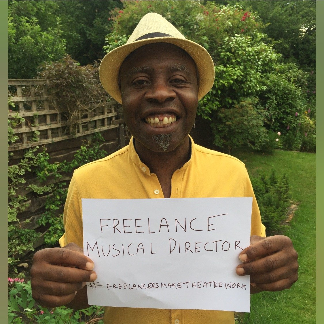 Photo of a musical director holding up a sign