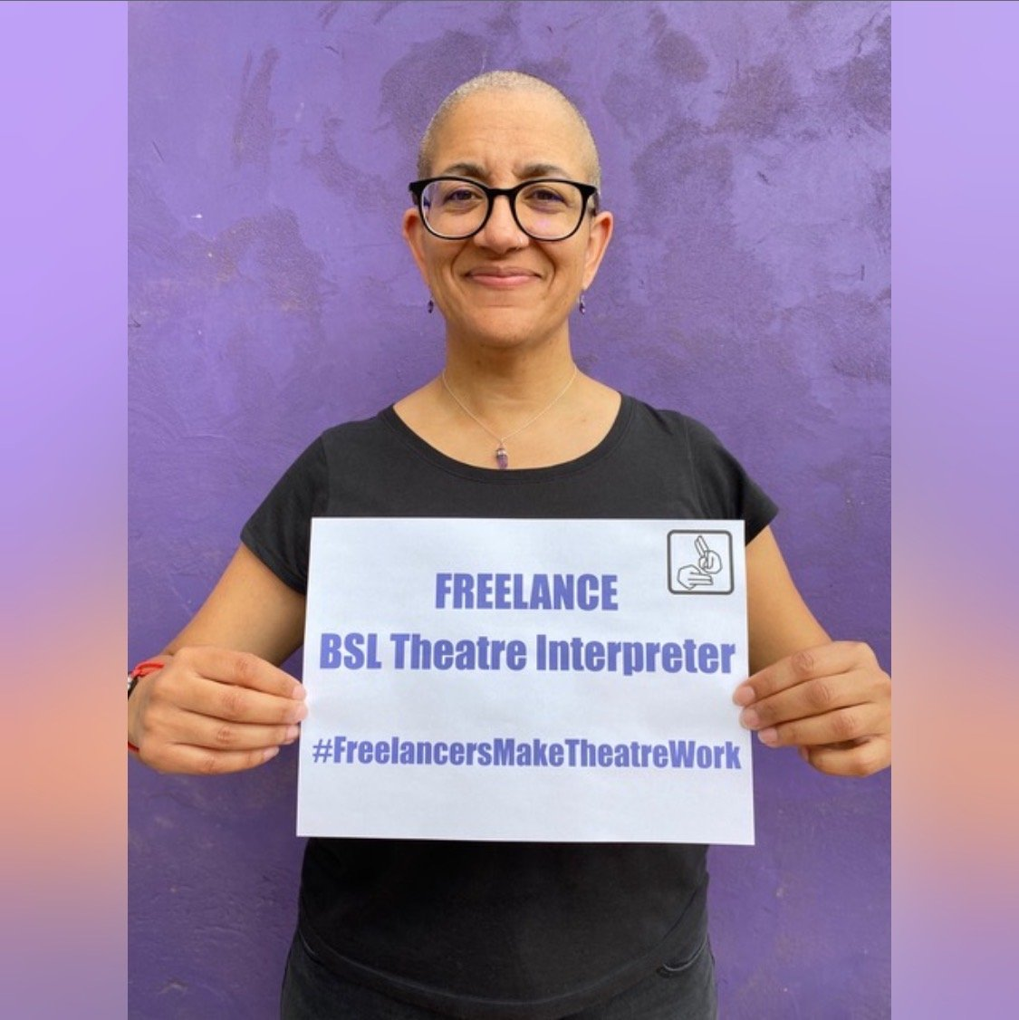 Photo of a BSL theatre interpreter holding up a sign