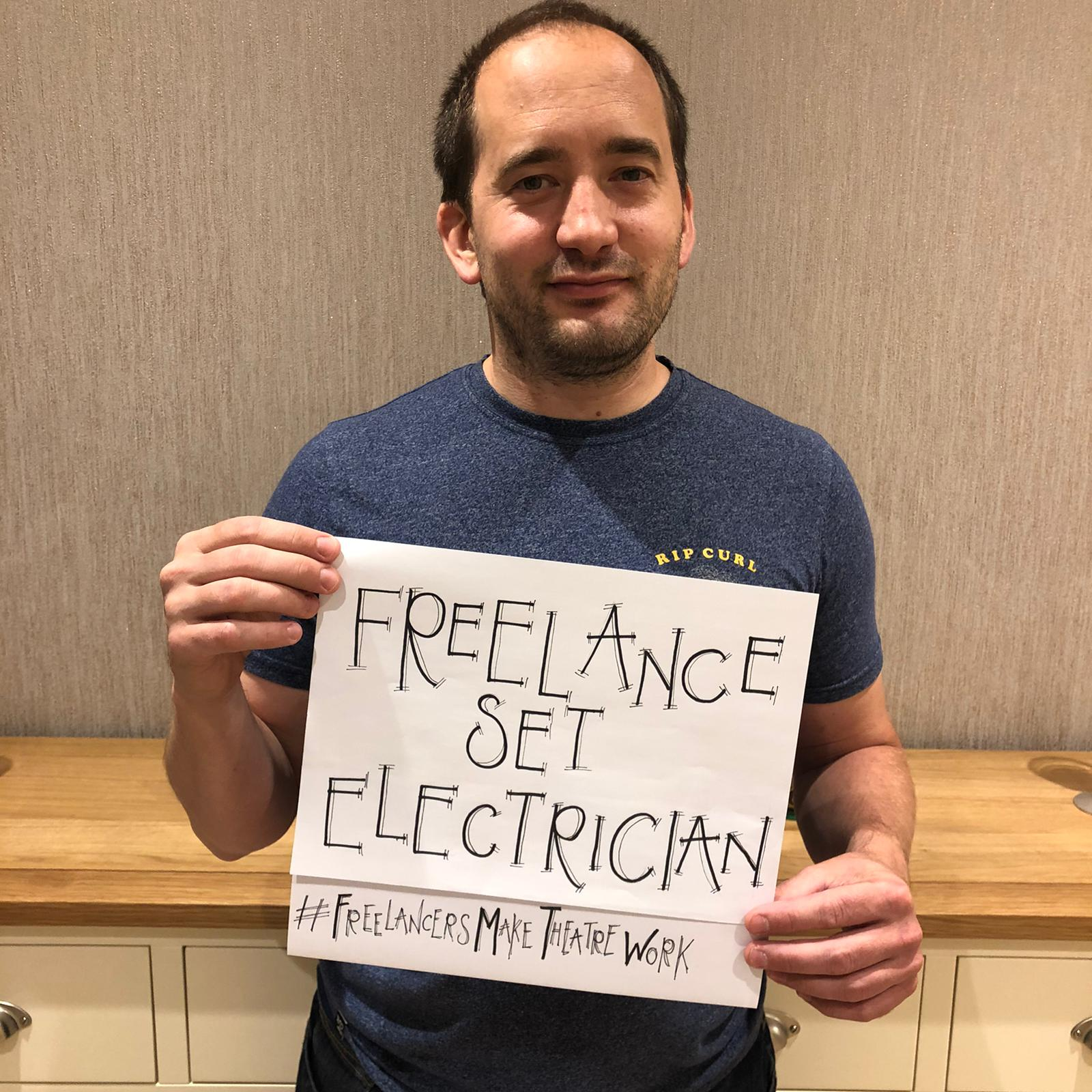 Photo of a freelance electrician holding up a sign