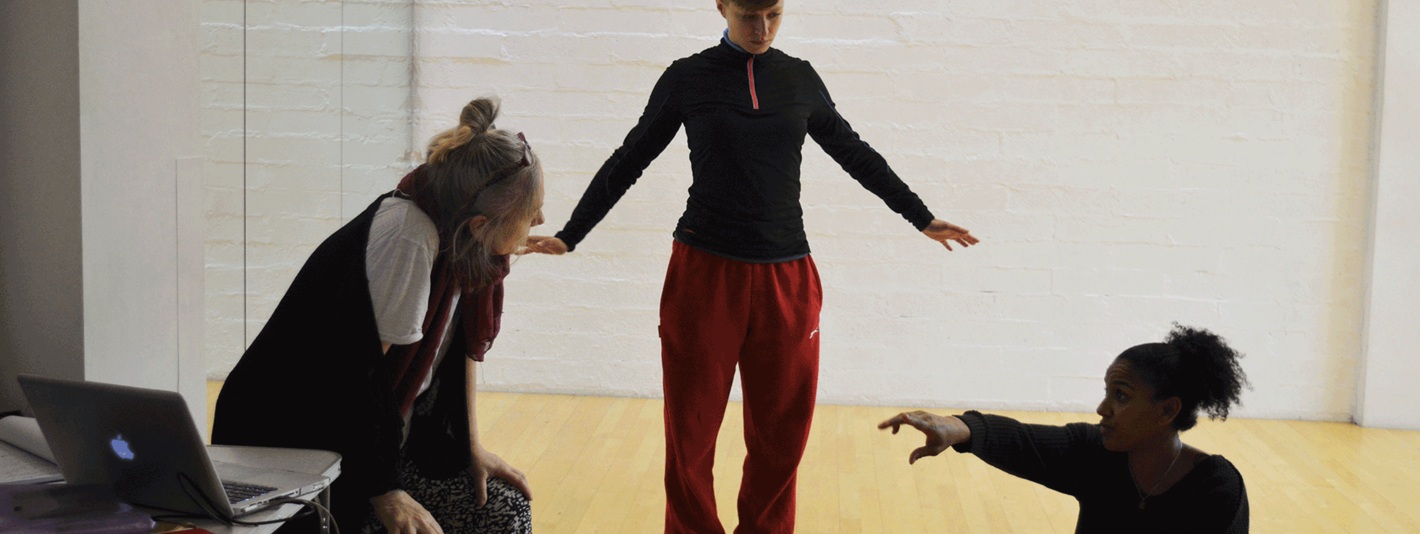 Three dancers in a rehearsal room