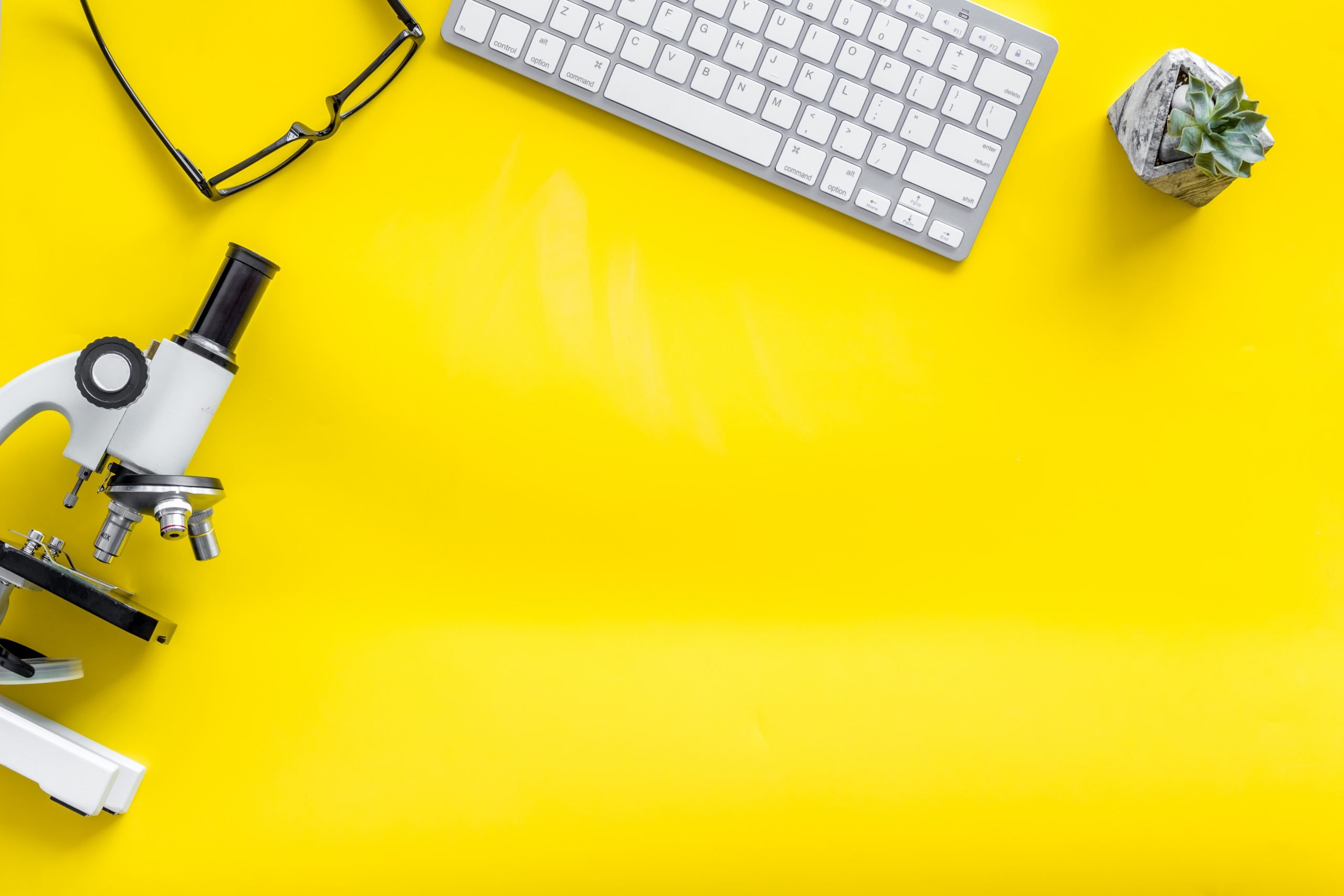 A keyboard, glasses, paper and microscope laid out on a yellow background