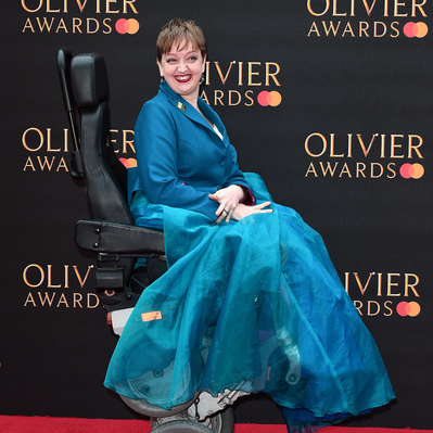 Athena Stevens in a long, blue dress. She is in a wheelchair on the red carpet of the Olivier Awards.